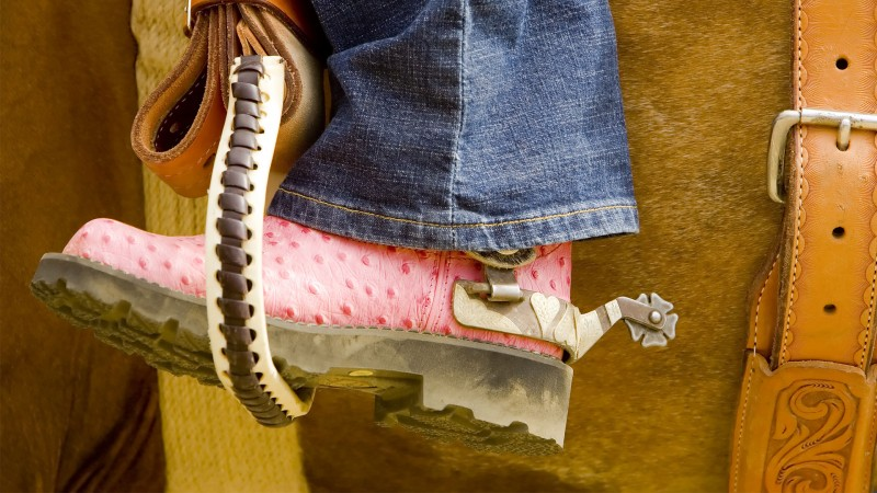 woman wearing pink cowboy boots is riding a horse