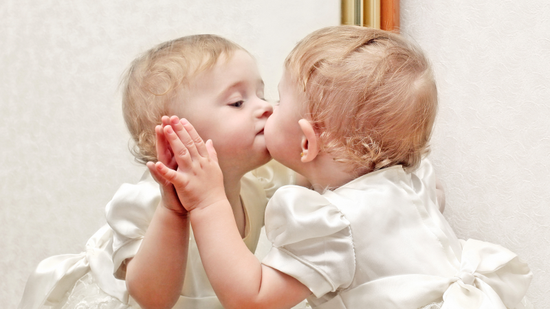 A little girl gives herself a kiss in a mirror.