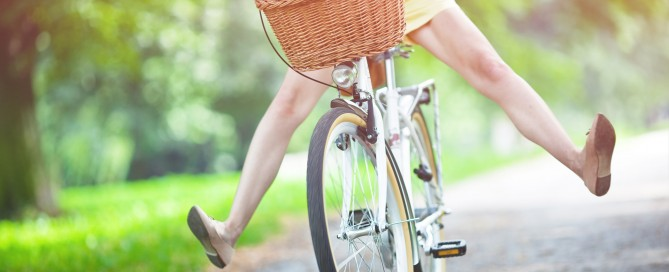 Middle-aged happy woman joyfully riding her bike with a wicker basket on it.